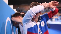 Atlet Komite Olahraga Rusia, Denis Abliazin mengusap air mata usai memenangkan final beregu putra senam artistik Olimpiade Tokyo 2020 di Ariake Gymnastics Center di Tokyo, Senin (26/7/2021). (Foto: AFP/Martin Bureau)