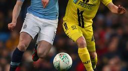 Gelandang Manchester City, Kevin De Bruyne berebut bola dengan pemain Burton Albion, Jamie Allen pada laga leg pertama semifinal Piala Liga Inggris di Stadion Etihad, Kamis (10/1). Manchester City menang telak atas Burton Albion 9-0. (AP/Dave Thompson)