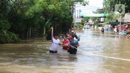 Warga berusaha melintasi banjir yang merendam perumahan Ciledug Indah, Tangerang, Banten, Kamis (2/1/2020). Memasuki hari kedua, kondisi perumahan tersebut masih tergenang banjir setinggi dada orang dewasa. (Liputan6.com/Angga Yuniar)