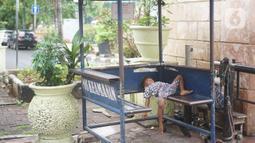 Seorang anak tidur di sebuah pos Pasar Baru, Jakarta Pusat, Senin (4/5/2020). Adanya program PSBB menyebabkan hampir seluruh pertokoan di salah satu pusat tekstil Ibukota tersebut berhenti beroperasi dan lebih sepi dibanding hari biasa. (Liputan6.com/Immanuel Antonius)