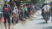Sejumlah penyapu koin kali Sewo menunggu di sepanjang pinggir jalan, Subang, Jawa Barat, Sabtu (7/1). Mereka menunggu pengendara yang lewat melempar koin ke jalan. (Liputan6.com/Helmi Afandi)