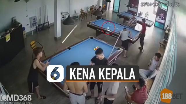 Pemuda itu menyodok bola billiard hingga keluar area permainan dan mengenai kepala pemuda lain yang sedang bermain billiard di meja lain.