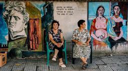 Warga duduk di depan lukisan mural seniman terkenal di  dinding desa Staro Zhelezare, Bulgaria, 4 Agustus 2018. Mural bagian dari proyek tahunan itu diluncurkan oleh wanita Polandia, Katarzyna Piriankov dan suaminya, Ventzislav. (AFP/Dimitar DILKOFF)