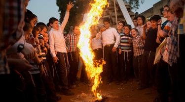 Pemuda Yahudi Ultra Ortodoks bermain api selama liburan Yahudi Lag Ba'Omer di Bnei Brak, Israel (2/5). Perayaan Lag Ba'Omer ini menandai berakhirnya musim wabah menurut kepercayaan mereka. (AP Photo / Oded Balilty)