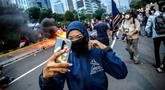 Pendemo berselfie di kobaran api saat aksi unjuk rasa di kawasan patung kuda, Jakarta, Selasa (20/10/2020). Gelombang protes tolak UU Cipta Kerja belum surut sejak disahkan pada 5 Oktober lalu. (Liputan6.com/Faizal Fanani)