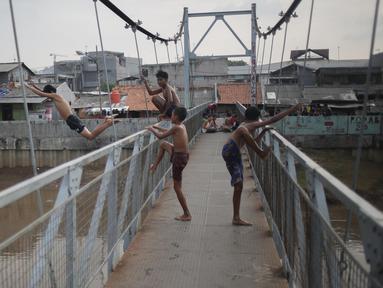 Seorang anak melompat dari atas jembatan dan berenang di aliran kali besar Banjir Kanal Barat, Jakarta, Sabtu (11/3). Minimnya pengawasan orang tua membuat mereka bermain di tempat berbahaya dan mengancam keselamatan. (Liputan6.com/Faizal Fanani)