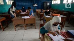 Suasana pembagian raport secara bergilir di SMP Negeri 18 Tangerang Selatan, Banten, Kamis (17/12/2020). Dalam pembagian raport, pihak sekolah menerapkan pola physical distancing atau jaga jarak. (merdeka.com/Dwi Narwoko)
