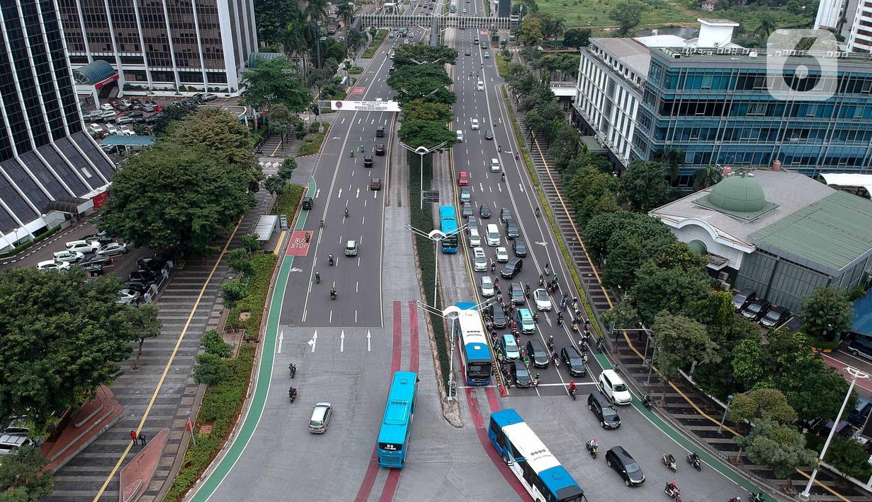 Foto aerial kendaraan melintas di Jalan Jenderal Sudirman, Jakarta, Selasa (24/3/2020). Sejumlah ruas jalan utama ibu kota lebih lengang dibandingkan hari biasa karena sebagian perusahaan telah menerapkan bekerja dari rumah guna menekan penyebaran COVID-19. (Liputan6.com/Faizal Fanani)