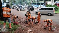 Petugas PPSU atau yang lebih dikenal dengan sebutan Pasukan Oranye membersihkan sendimen tanah merah yang longsor ke jalan Galunggung, Jakarta, Selasa (30/8/2016). (Liputan6.com/Yoppy Renato)