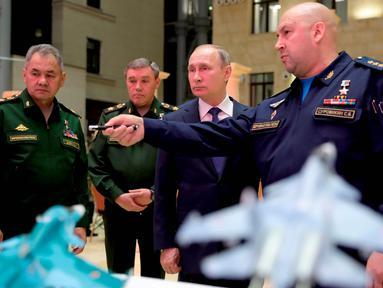 Presiden Rusia Vladimir Putin (kedua kanan) mendengarkan Komandan Angkatan Udara Rusia Sergei Surovkin (kanan) saat mengunjungi sebuah pameran di markas militer Rusia di Moskow (30/1). (Mikhail Klimentyev, Sputnik, Kremlin Pool/AP)