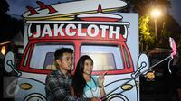 Dua orang pengunjung berfoto di salah satu stand di JakCloth 2015 di Parkir Timur Senayan Jakarta, Rabu (30/12/2015). JakCloth 2015 berlangsung pada 30 Desember 2015 hingga 3 Januari 2016. (Liputan6.com/Helmi Fithriansyah)