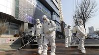 Para pekerja yang mengenakan pakaian pelindung menyemprotkan desinfektan terhadap virus corona baru di depan sebuah gereja di Daegu, Korea Selatan, Kamis, 20 Februari 2020. (Kim Jun-beom / Yonhap via AP)