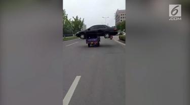 Sebuah kendaraan roda tiga mengangkut mobil sedan dan melaju di jalan raya Kota Huzhou. Polisi akhirnya memberikan denda kepada si pengemudi.