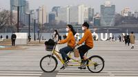 Sepasang kekasih mengenakan masker saat bersepeda  di sebuah taman di Seoul, Korea Selatan, 7 Maret 2020. Hingga Kamis (12/3/2020) pagi, jumlah kasus virus corona COVID-19 di Korea Selatan sebanyak 7.755 orang terinfeksi, 60 meninggal, dan 288 sembuh. (AP Photo/Ahn Young-joon)