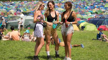 Tiga wanita berbincang saat hari ketiga Festival Glastonbury di Worthy Farm, Somerset, Inggris (28/6/2019). Festival Glastonbury merupakan festival musik paling populer di dunia yang berlangsung lima hari. (AP Photo/Joel C Ryan)