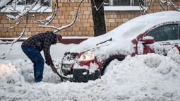 Seorang pria menggali untuk memindahkan mobilnya usai dilanda badai salju di Moskow (5/2). Suhu udara di sana mencapai minus 34 derajat celcius. (AFP/Vasily Maximov)