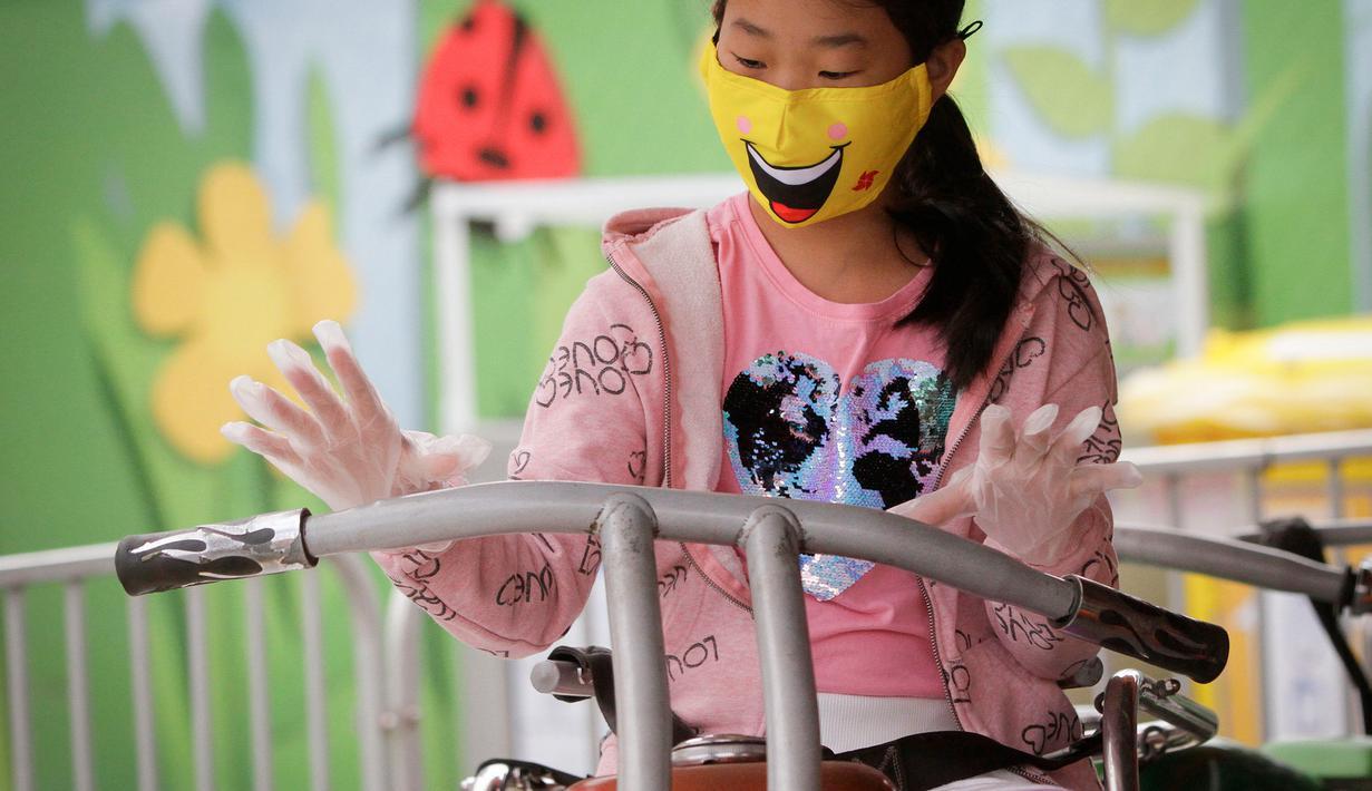 Seorang anak yang mengenakan masker dan sarung tangan menaiki wahana di Playland Amusement Park, di Vancouver, British Columbia, Kanada, pada 10 Juli 2020. Playland Amusement Park dibuka kembali untuk umum pada Jumat (10/7), dengan langkah-langkah protokol kesehatan. (Xihua/Liang Sen)