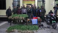 Yonif Raider 756/WMS menyerahkan pelaku pengedar ganja dan barang bukti ke Kapolres Jayawijaya AKBP Yan Reba (3/8). Mereka berhasil mengamankan Sajam, atribut/bendera Bintang Kejora, Miras dan 95, 20 gram ganja kering siap edar. (Liputan6.com/HO/Dispenad)