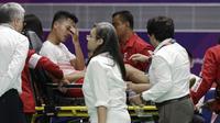 Pebulutangkis Indonesia, Anthony Ginting, ditandu keluar lapangan karena cedera saat melawan wakil China, Shi Yuqi, pada laga final bulutangkis beregu putra Asian Games di Istora, Jakarta, Rabu (22/08/2018). (AP/Aaron Favila)