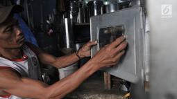 Pekerja menyelesaikan pembuatan oven di salah satu toko kawasan Cawang, Jakarta, Minggu (19/5/2019). Harga oven yang ditawarkan bervariasi dari Rp120 ribu-Rp 2 juta tergantung ukuran dan jenis bahan. (merdeka.com/Iqbal Nugroho)