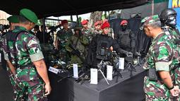 Tentara memperlihatkan jenis-jenis senjata saat apel pengamanan Pemilu 2019 di Bogor, Jawa Barat, Rabu (10/4). Apel dihadiri Panglima TNI Marsekal Hadi Tjahjanto dan Kapolri Jenderal Tito Karnavian. (ADEK BERRY/AFP)