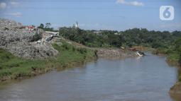 Pekerja menggunakan alat berat mengeruk sampah yang longsor di TPA Cipeucang, Serpong, Tangerang Selatan, Banten, Sebtu (23/5/2020). Turap penahan sampah TPA Cipeucang longsor pada 22 Mei 2020 dan hampir menutupi aliran Sungai Cisadane yang berada di sebelahnya. (merdeka.com/Dwi Narwoko