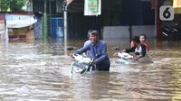 Warga membawa motor melintasi banjir yang merendam jalan Raya KH Hasyim Ashari, Ciledug ,Tangerang, Rabu (1/1/2020). Banjir setinggi dada orang dewasa membuat jalur penghubung Tangerang ke Jakarta tersebut terputus tidak dapat dilintasi. (Liputan6.com/Angga Yuniar)