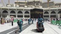 Para pekerja membersihkan Masjidil Haram saat kegiatan umrah di kota suci Muslim Mekah, Arab Saudi, Senin, (2/3/2020). Semenjak pemerintah Arab Saudi melarang kegiatan umrah, tempat paling suci umat Islam ini menjadi terlihat lebih sepi dari biasanya. (AP Photo/Amr Nabil)