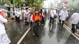 Seorang petugas kebersihan DKI Jakarta membawa kantung plastik untuk membersihkan sampah  usai aksi damai 2 Desember di kawasan Jalan MH Thamrin, Jakarta, Jumat (2/12). (Liputan6.com/Ferbian Pradolo)