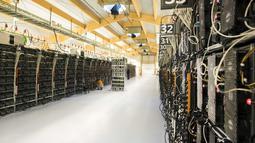 Seorang teknisi melakukan perawatan pada rig pertambangan dari komputer super di dalam pabrik bitcoin 'Genesis Farming' di dekat Reykjavik, Islandia (16/3). (AFP Photo/Halldor Kolbeins)