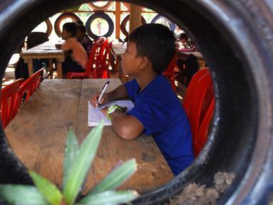 Siswa belajar di ruang kelas berdinding ban mobil yang dicat di Coconut School, Taman Nasional Kirirom Kamboja, 1 Oktober 2018. Sekolah ini didirikan mantan manajer sebuah hotel, Ouk Vanday yang mendambakan Kamboja bebas sampah. (TANG CHHIN Sothy/AFP)
