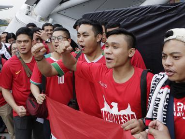 Suporter Timnas Indonesia menyanyikan lagu saat berada di Stadion Nasional, Singapura, Jumat (9/11). Indonesia akan melawan Singapura pada laga Piala AFF 2018. (Bola.com/M. Iqbal Ichsan)