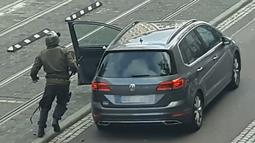 Seorang pria berlari menuju mobil sambil membawa senjata di jalanan Halle an der Saale, Halle, Jerman, Rabu (9/10/2019). Gagal menembus penjagaan sinagoge, pelakuk bergeser dan menyerang toko kebab. (Andreas Splett/ATV-Studio Halle/AFP)