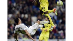 Cristiano Ronaldo melakukan tendangan salto saat dihadang pemain Villarreal, Eric Bally, pada lanjutan La Liga Spanyol di Stadion Santiago Bernabeu, Madrid, Rabu (20/4/2016) atau Kamis dini hari WIB. (AFP/Javier Soriano)