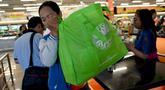 Seorang konsumen menggunakan tas belanja nonplastik untuk mengemas barang belanjaan di sebuah supermarket di Denpasar, 16 Juli 2019. Bali menerapkan pelarangan penggunaan plastik sekali pakai yang tertuang dalam Peraturan Gubernur (Pergub) Nomor 97 Tahun 2018. (SONNY TUMBELAKA/AFP)