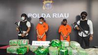 Dua tersangka kurir narkoba dengan barang bukti 20 kilogram sabu di Polda Riau. (Liputan6.com/M Syukur)