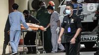 Tim forensik menurunkan kantong jenazah berisi serpihan Sriwijaya Air SJ 182 dan diduga tubuh korban dari ambulans di RS Polri, Jakarta, Minggu (10/1/2021). RS Polri menerima tiga kantong jenazah berisi serpihan pesawat dan diduga tubuh korban untuk diidentifikasi. (merdeka.com/Iqbal S. Nugroho)