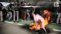 Massa yang tergabung dalam gerakan nasional tolak reklamasi (Gentar) membakar ban saat aksi didepan Gedung Balaikota, Jakarta, Rabu (8/7/2020). Reklamasi Pantai Ancol dianggap sebagai bentuk perampasan pantai publik atas akses masyarakat nelayan pesisir Jakarta.  (Liputan6.com/Faizal Fanani)