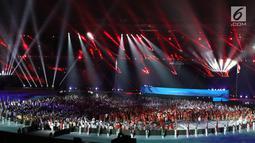 Parade atlet dari berbagai negara saat upacara Penutupan Asian Games 2018 di Stadion Utama Gelora Bung Karno, Jakarta, Minggu (2/9). Mereka mengenakan jas hujan yang mengguyur Jakarta. (Liputan6.com/Helmi Fithriansyah)