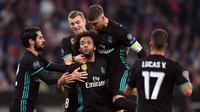 Pemain Real Madrid, Marcelo mendapat ucapan dari rekan timnya usai mencetak gol ke gawang Bayern Munchen pada leg pertama semifinal Liga Champions di Allianz Arena, Rabu (25/4). Real Madrid berhasil menumbangkan Bayern Munchen 2-1. (Sven Hoppe/dpa via AP)