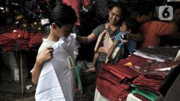 Pembeli mencoba seragam sekolah di Pasar Jatinegara, Jakarta, Minggu (5/1/2020). Jelang hari pertama belajar di semester baru, warga terdampak banjir di Kampung Melayu dan sekitarnya terpaksa membeli seragam baru untuk anaknya akibat banjir yang merendam rumah mereka. (merdeka.com/Iqbal Nugroho)