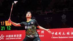 Tunggal putra Indonesia, Anthony Ginting, berusaha mengembalikan kok saat melawan tunggal Jepang, Kento Momota, pada BWF World Tour 2019 di Tianhe Gymnasium, Guangzhou, Minggu (15/12). Ginting kalah 21-17, 17-21 dan 14-21 dari Momota. (AFP/STR)