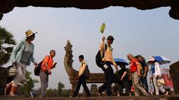 Turis mengunjungi candi Angkor Wat di provinsi Siem Reap, barat laut Kamboja pada 16 Maret 2019. Pada tahun 1992, Angkor Wat masuk ke dalam daftar Situs Warisan Dunia UNESCO. (TANG CHHIN Sothy / AFP)