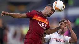 Bek AS Roma, Bruno Peres menyundul bola saat berduel dengan penyerang Sevilla, Munir El Haddadi pada babak 16 besar Liga Europa di Stadion Schauinsland-Reisen-Arena, Kamis (6/8/2020). Sevilla lolos ke perempat final setelah mengandaskan AS Roma dengan skor 2-0. (Friedemann Vogel/Pool Photo via AP)