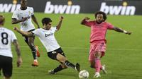 Bek Real Madrid, Marcelo (kanan) berebut bola dengan gelandang Valencia, Carlos Soler pada lanjutan La Liga di Stadion Mestalla, Selasa (9/11/2020) dinihari WIB. Real Madrid kalah telak 1-4 dari tuan rumah Valencia. (AP Photo/Alberto Saiz)