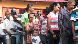 Seorang anak terlihat dalam antrean warga Timor Leste yang akan menggunakan hak pilih mereka di tempat pemungutan suara (TPS) yang berada di Dili, Senin (20/3). Sedikitnya 1,2 juta warga akan memilih presiden baru Timor Leste. (Valentino DARIEL SOUSA/AFP)