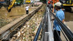 Warga melihat proses pengangkatan sampah dari jembatan Kampung Melayu, Jakarta, Minggu (3/4/2016). Akibat luapan Ciliwung, tumpukan sampah menyangkut di jembatan Kampung Melayu. (Liputan6.com/Yoppy Renato)