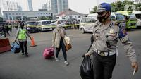 Polisi membantu membawakan barang penumpang yang terjaring razia travel gelap Ditlantas Polda Metro Jaya saat akan dipulangkan ke daerah asalnya, Jakarta, Kamis (29/4/2021). Sebanyak 115 kendaraan travel gelap diamankan. (Liputan6.com/Faizal Fanani)