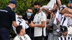Bukan hanya swafoto, Cristiano Ronaldo pun menyempatkan menandatangani baju bola bernomor punggung 7 milik salah satu penggemar. (Foto: AFP/Miguel Medina)
