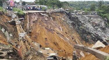 Permukaan jalan ambruk oleh tanah longsor yang disebabkan hujan lebat melanda distrik Lemba, Kinshasa di Republik Demokratik Kongo pada Selasa (26/11/2019). Musibah tersebut telah mengakibatkan jalan raya yang menjadi penghubung antar desa putus total. (AFP/Ange Kasongo)